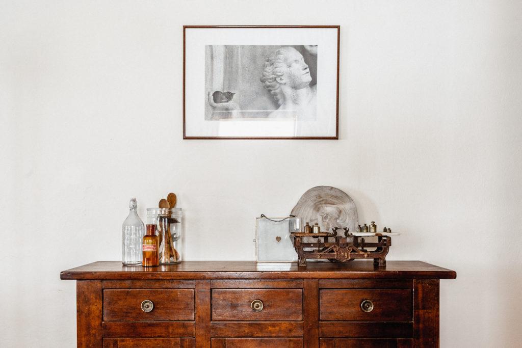 Fotografia di interni con comò antico, soprammobili rustici e quadro con gatto