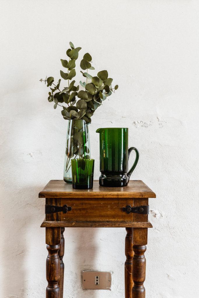Dettaglio di tavolino di legno antico con caraffa e bicchiere in vetro verde e vaso di eucalipto