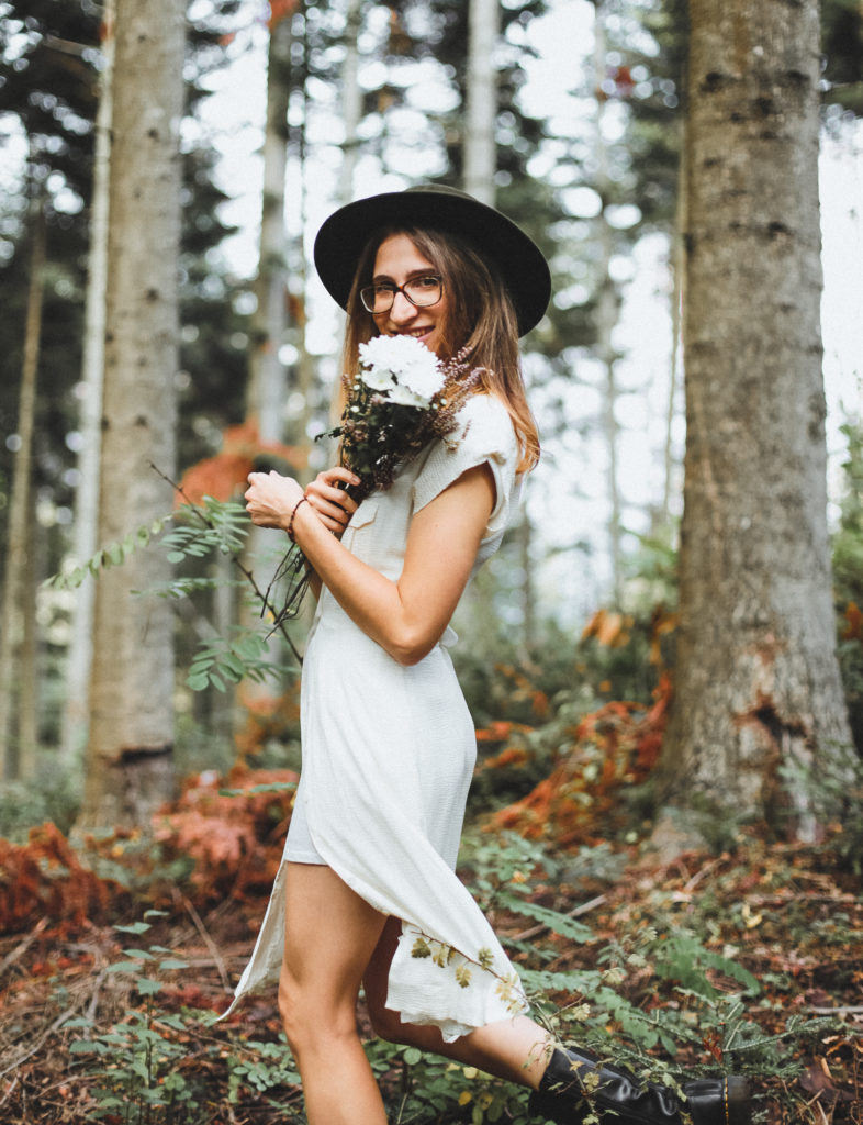 Ritratto di ragazza con abito bianco e cappello verde con mazzo di fiori in mezzo al bosco