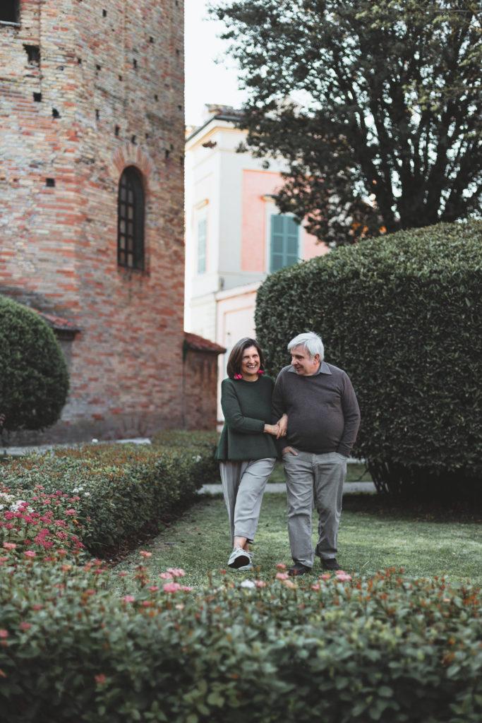 Coppia cinquantenne passeggia di fianco al battistero neoniano a Ravenna