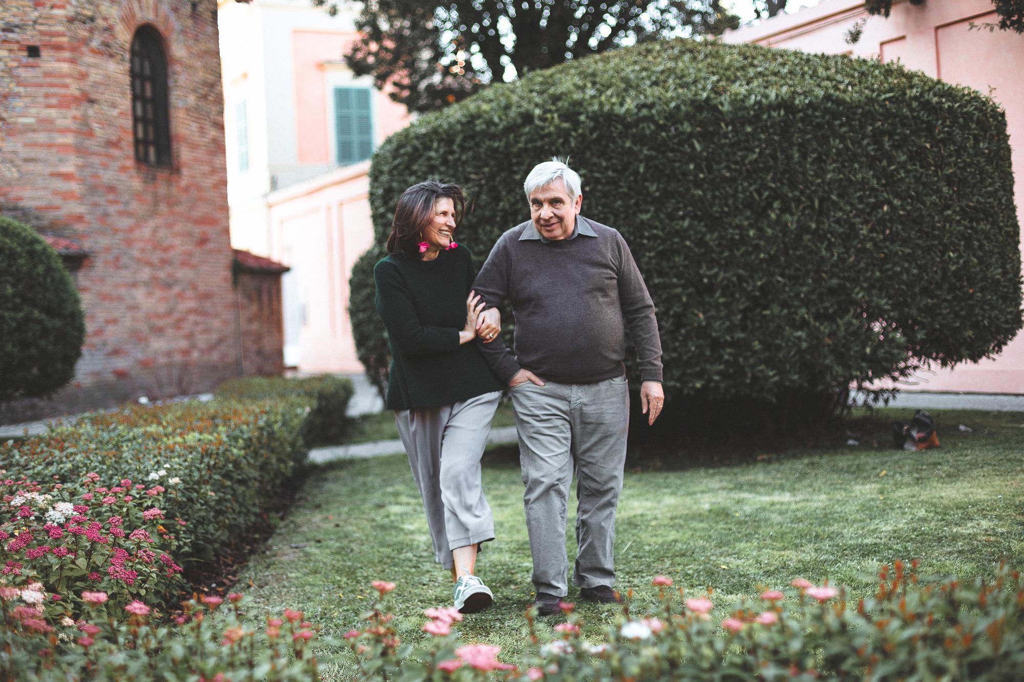 Coppia cinquantenne passeggia ridendo di fianco al battistero neoniano a Ravenna