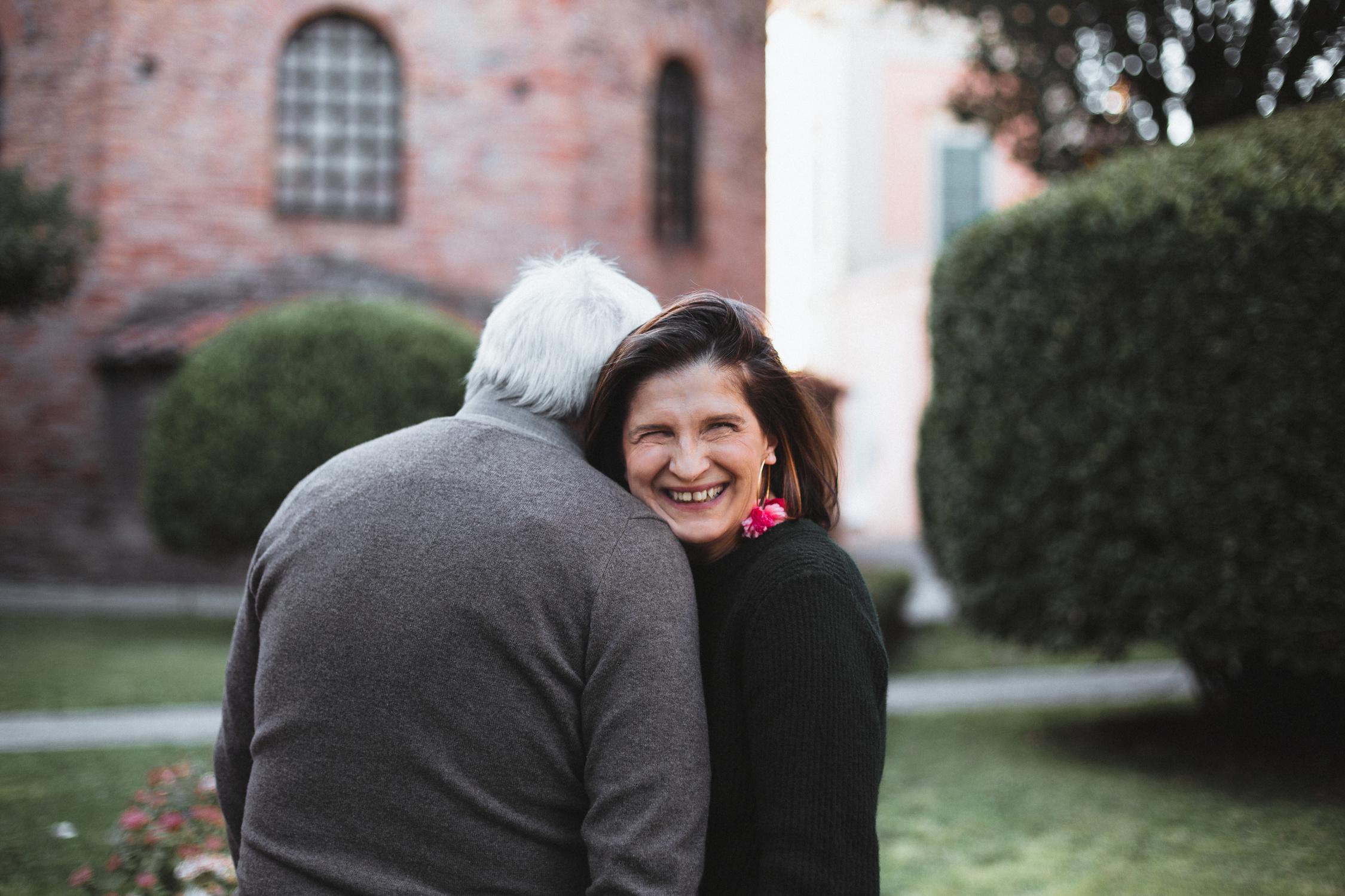 Donna sorridente appoggiata alla spalla di suo marito