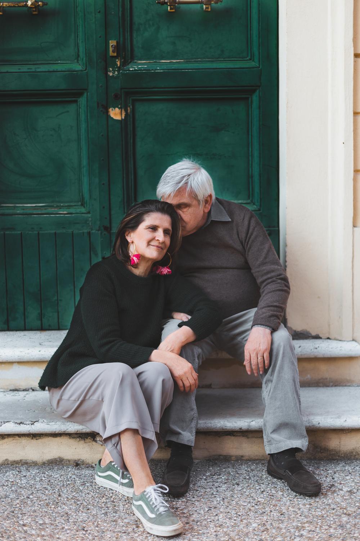 Coppia cinquantenne sorridente seduta davanti a un portone verde, marito che dà un bacio sulla testa alla moglie