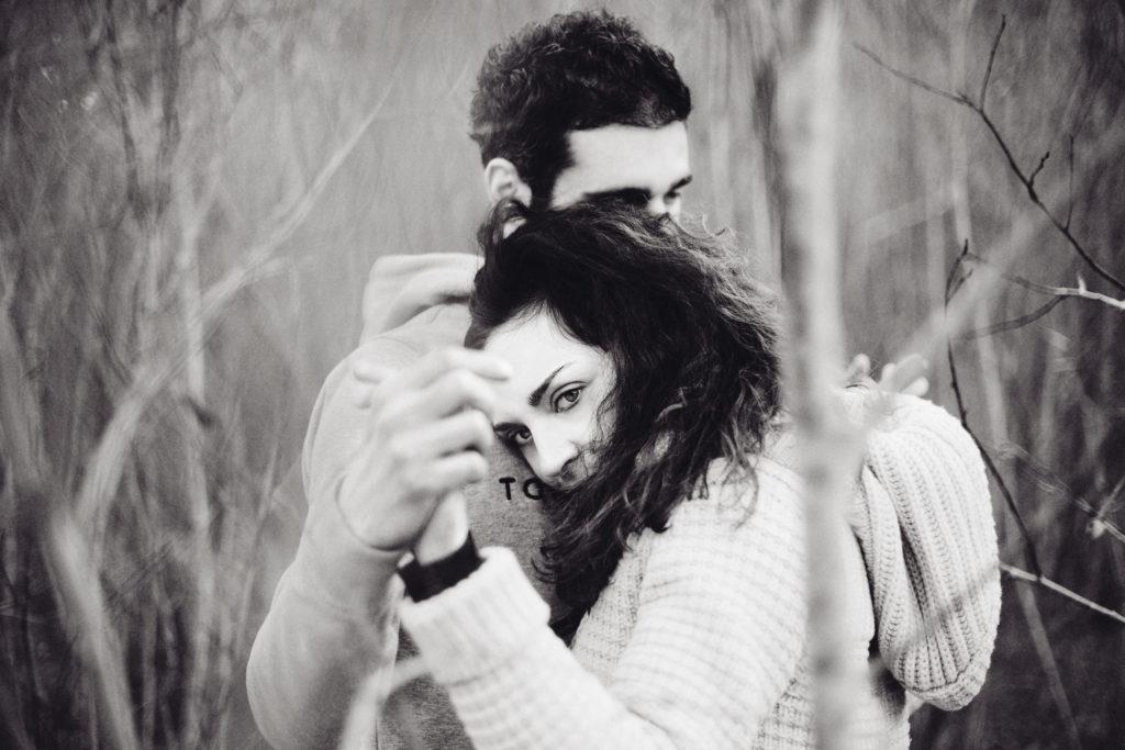 Coppia abbracciata in mezzo agli alberi invernali, ragazza con occhi chiari