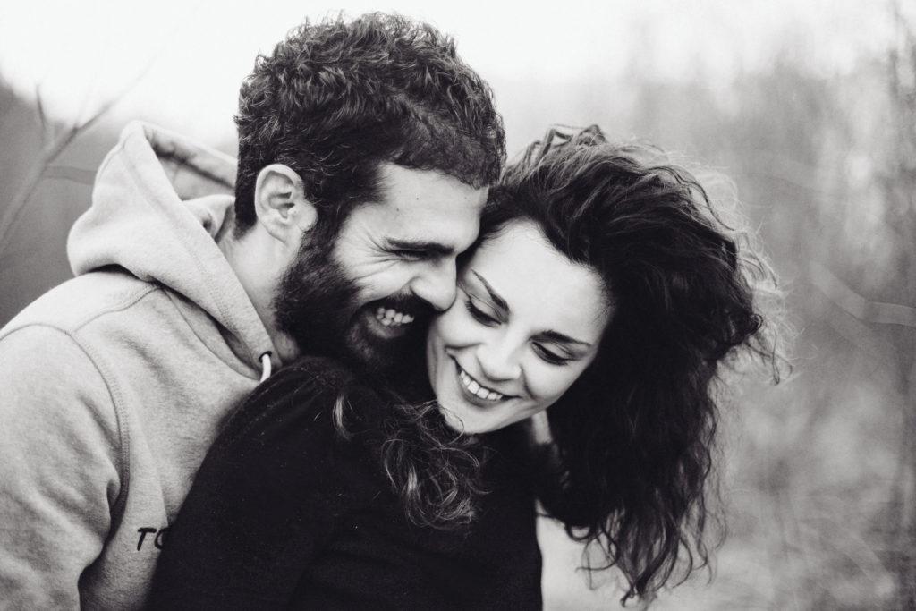 Ragazzo sorridente che sussurra all'orecchio della propria fidanzata