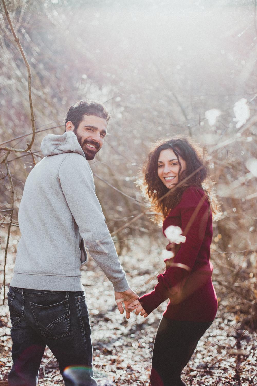 Coppia sorridente che cammina felice in mezzo alla rugiada invernale, con bokeh