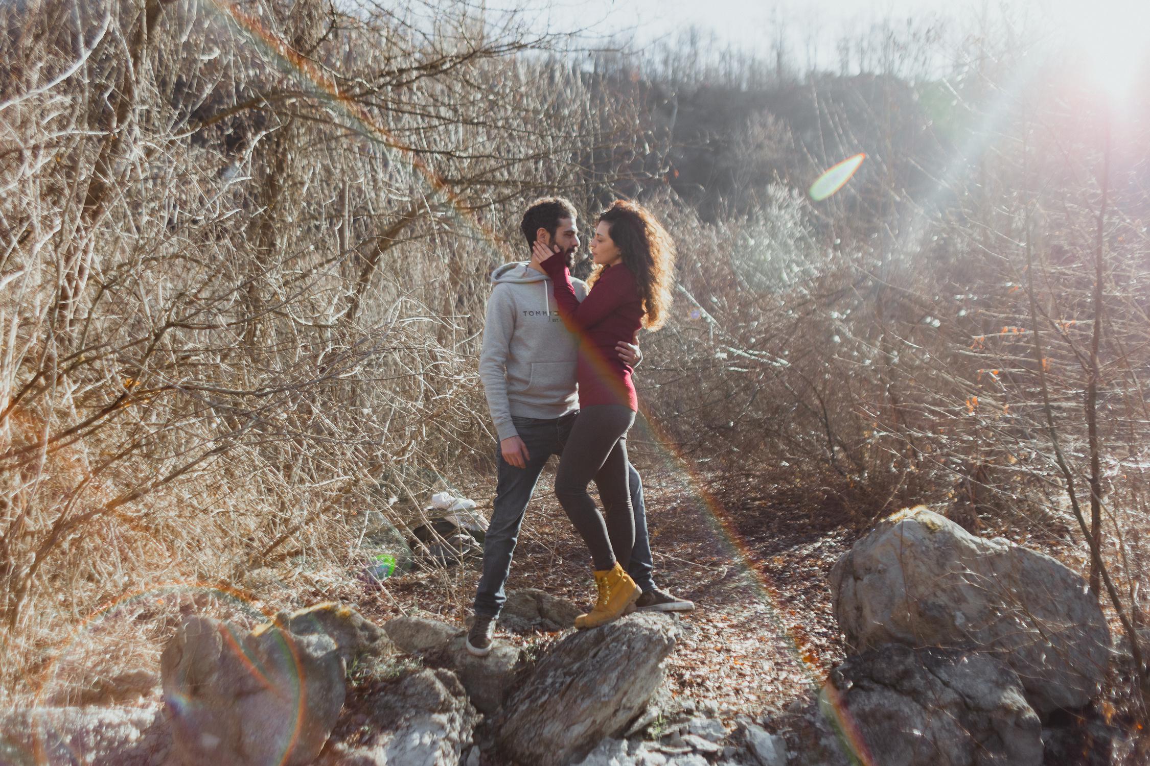 Coppia su una roccia in mezzo agli alberi invernali, con lens flare