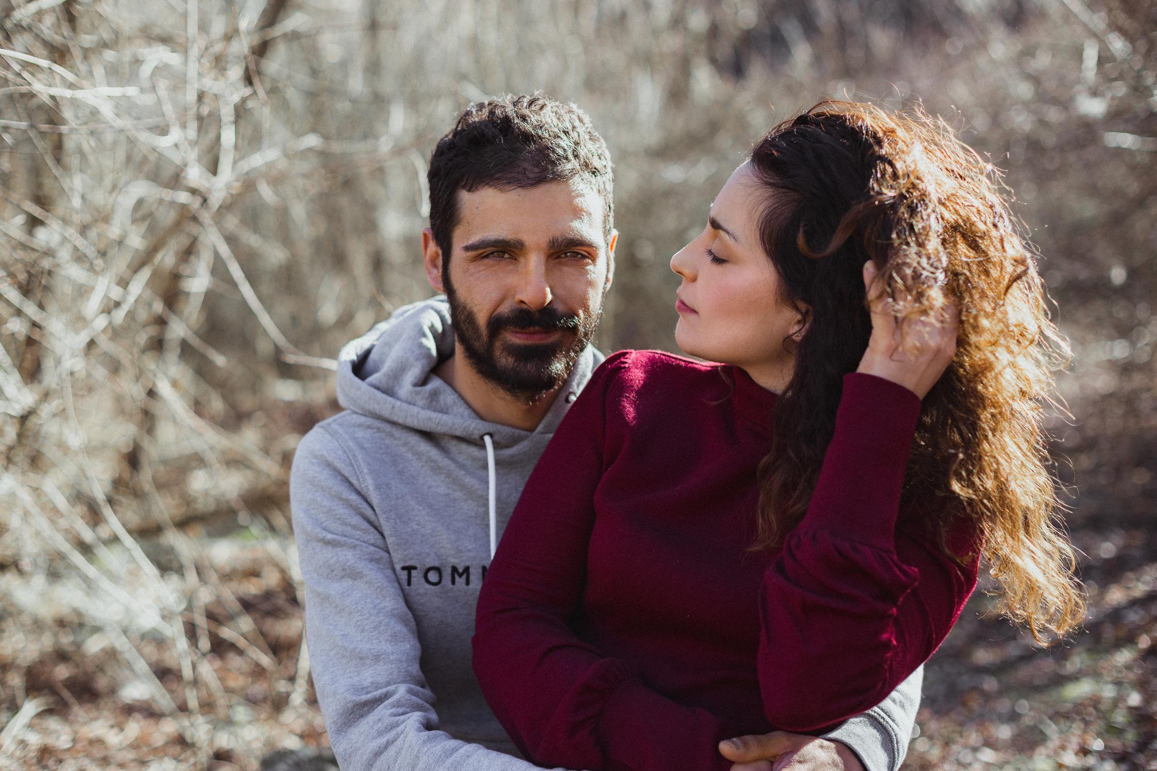 Ragazza con maglione rosso che guarda il proprio ragazzo, che guarda verso la macchina fotografica