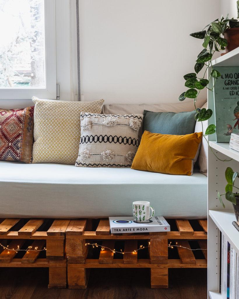 Fotografia di interni di salotto bohémien (bohemian) con divano fatto con bancali, fairy lights e cuscini boho