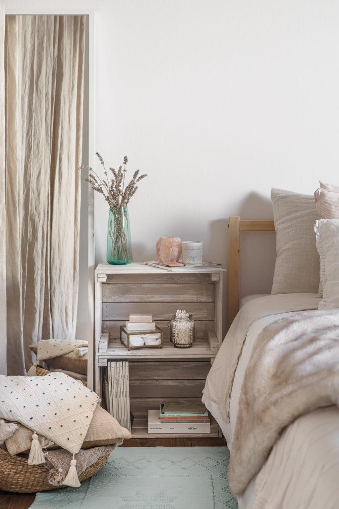 Fotografia di interni con letto con coperta pelosa, comodino di legno rustico, cuscini e vaso di lavanda