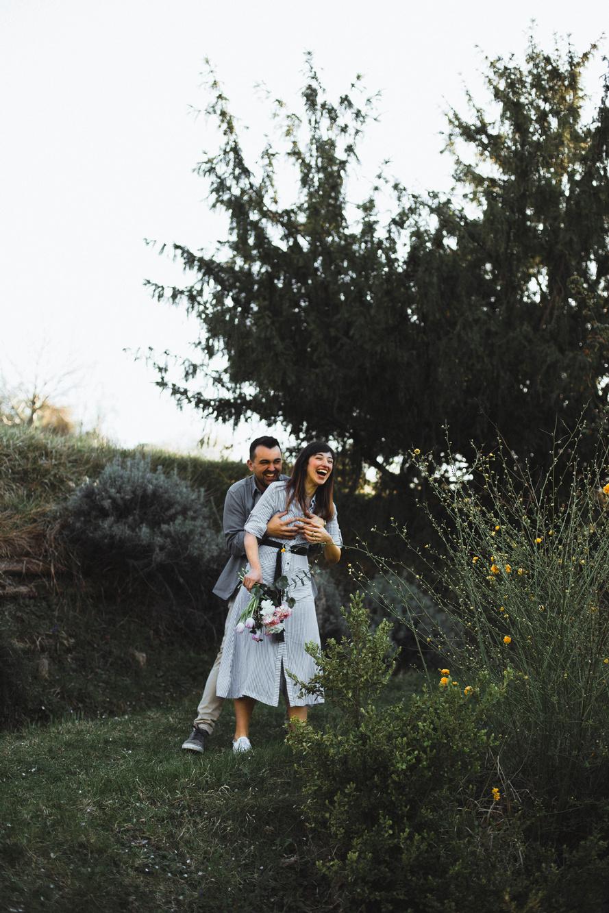 Ragazzo che fa uno scherzo alla propria ragazza, che ride, in mezzo ai fiori