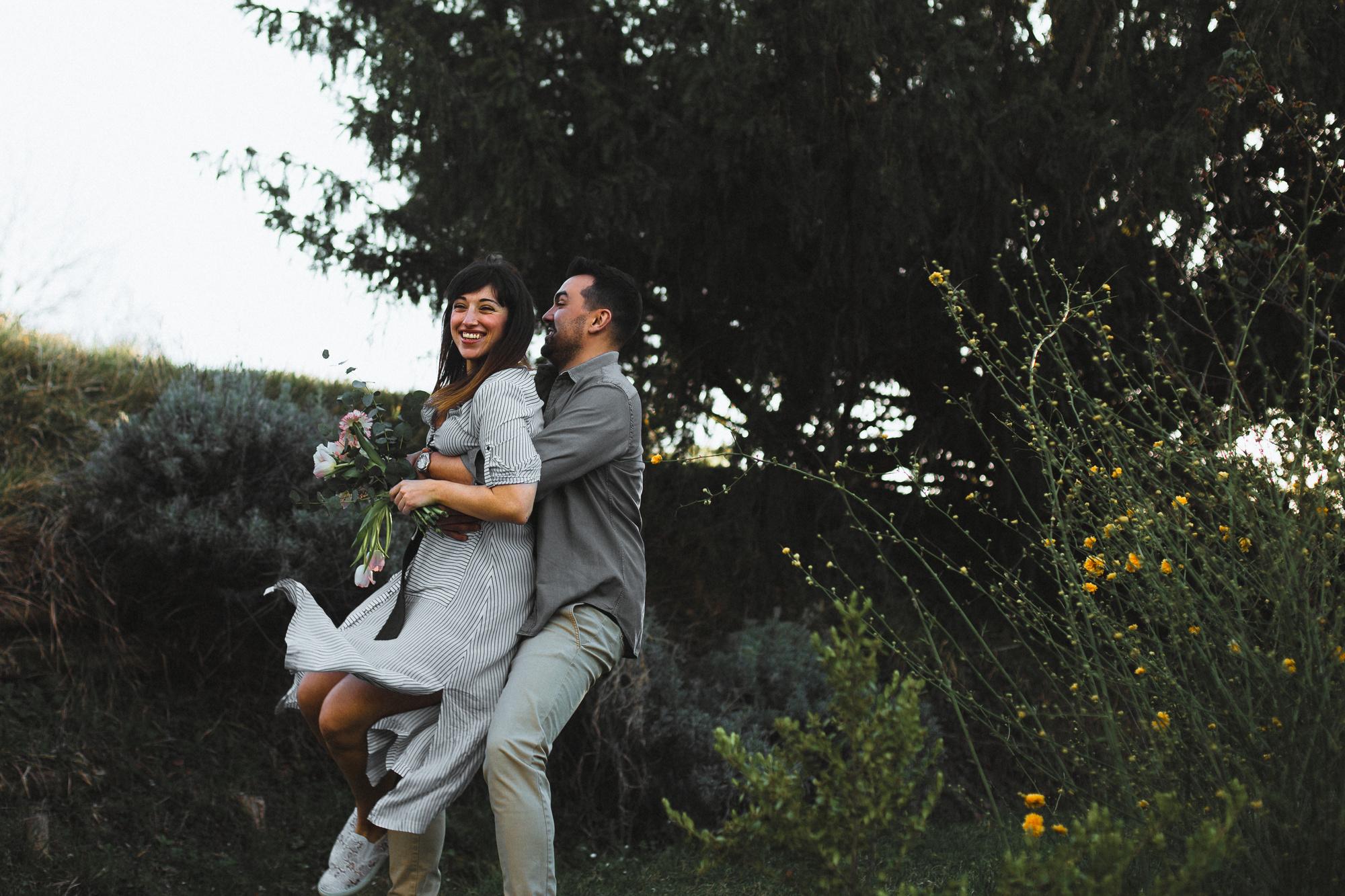 Ragazzo che prende in braccio la propria ragazza e gioca con lei, in mezzo ai fiori