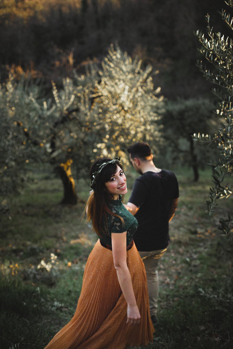 Coppia che cammina mano nella mano in mezzo agli ulivi, ragazza con corona di ulivo e vestito verde e arancione