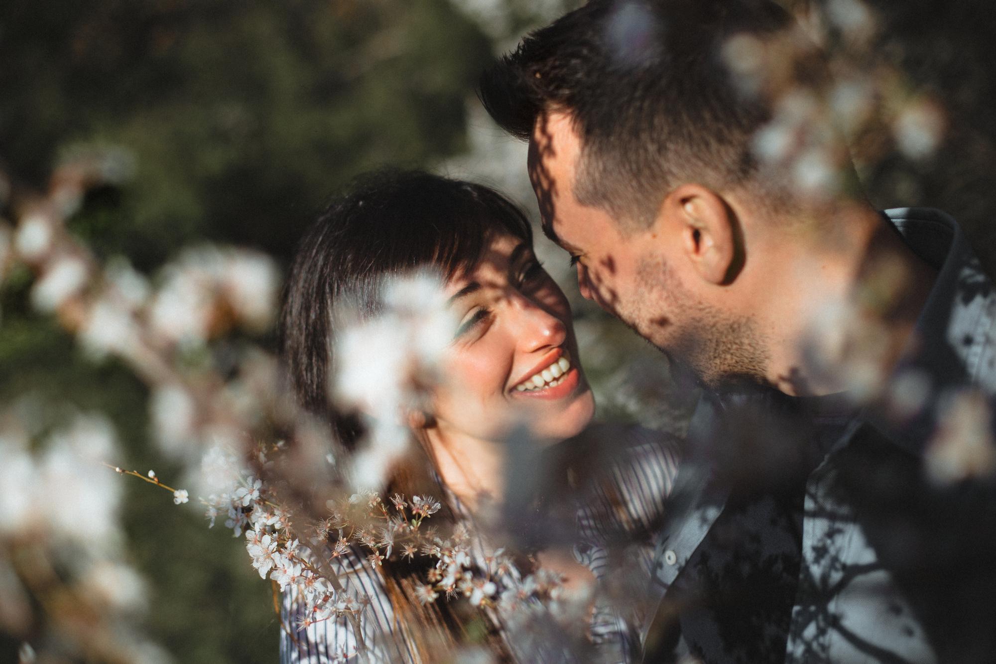 Primo piano di coppia sorridente in mezzo ai fiori di ciliegio