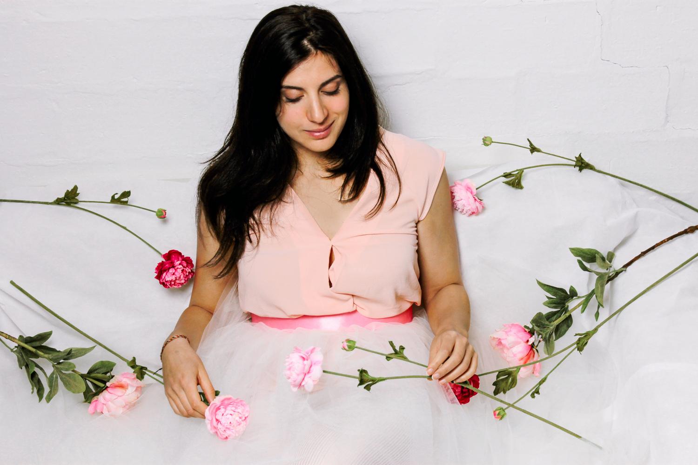 Ritratto di ragazza seduta con tulle e fiori