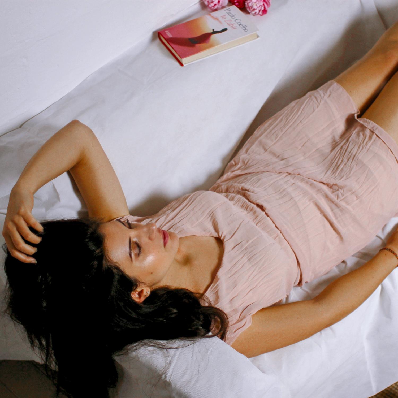 Ritratto di ragazza con vestito rosa sdraiata su divano