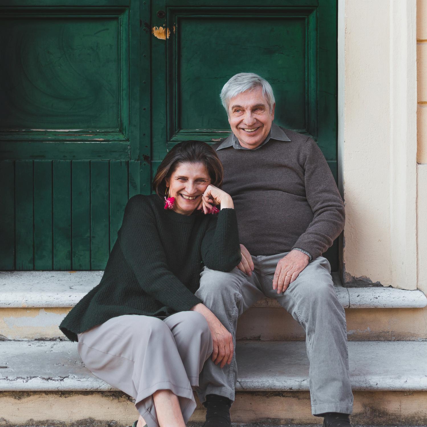 Coppia cinquantenne sorridente seduta davanti a un portone verde