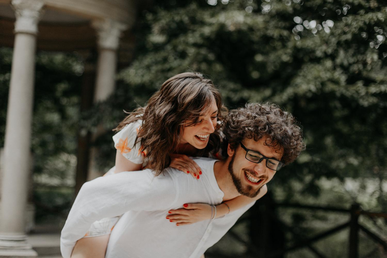 Ragazza castana che ride aggrappata alle spalle del suo fidanzato