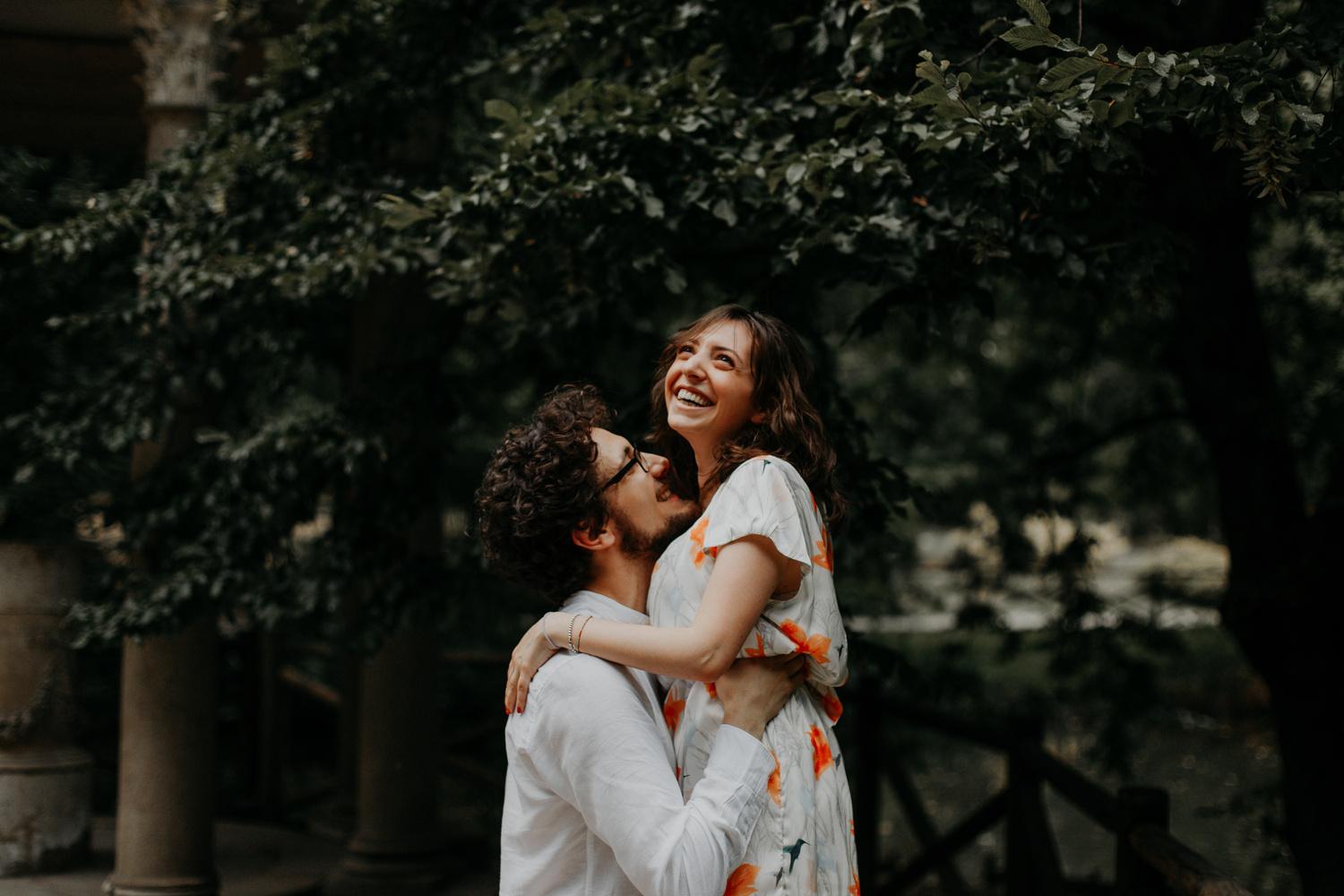 Ragazzo prende in braccio la sua fidanzata in un parco, mentre ridono