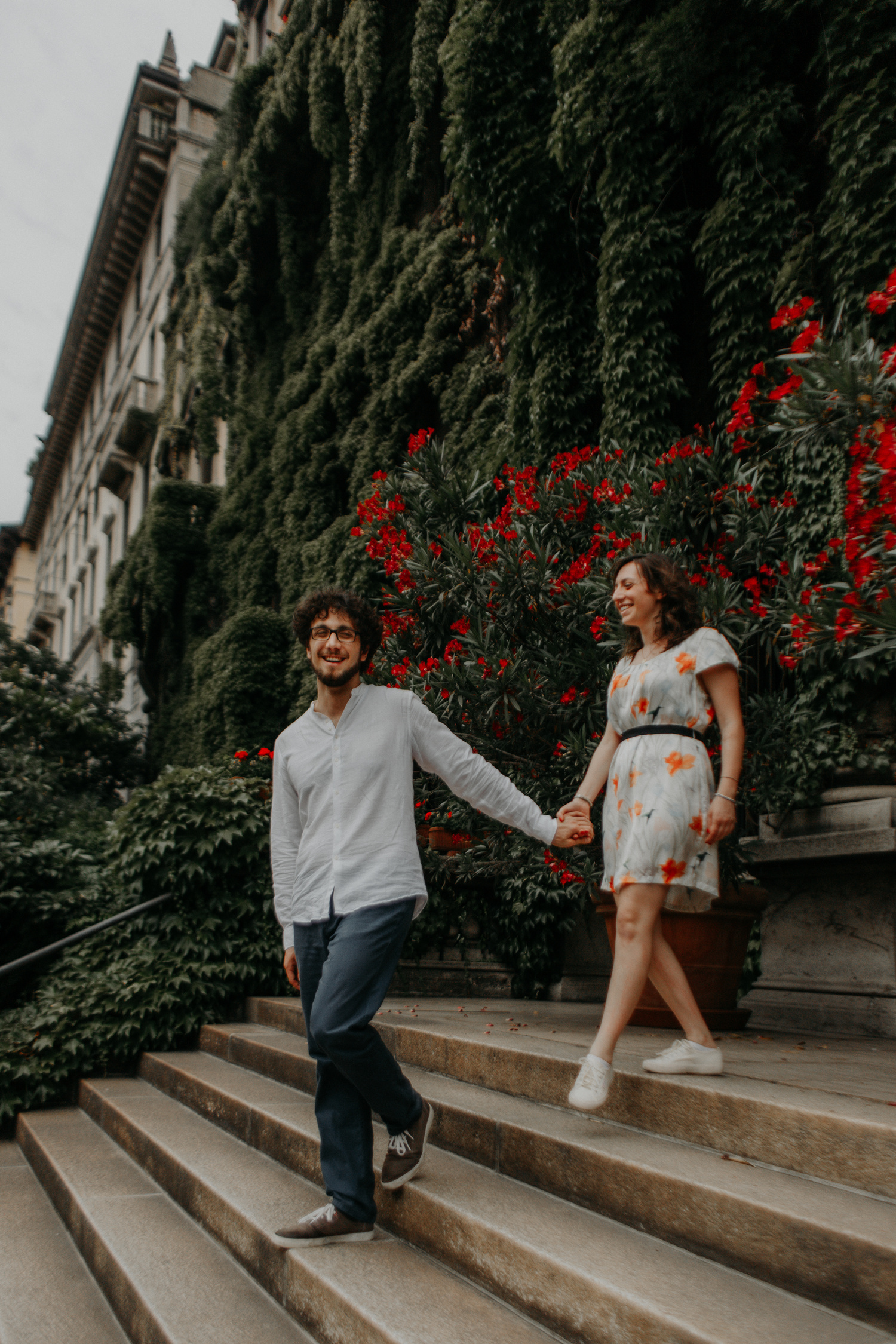 Coppia scende gradini di un palazzo di Milano con oleandri rossi sullo sfondo
