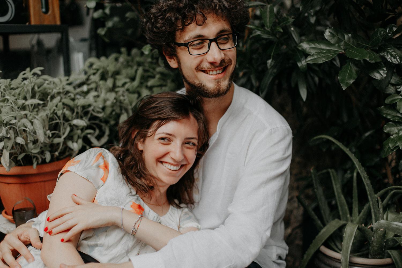 Coppia di fidanzati ride mentre si abbraccia seduta in un bar all'aperto