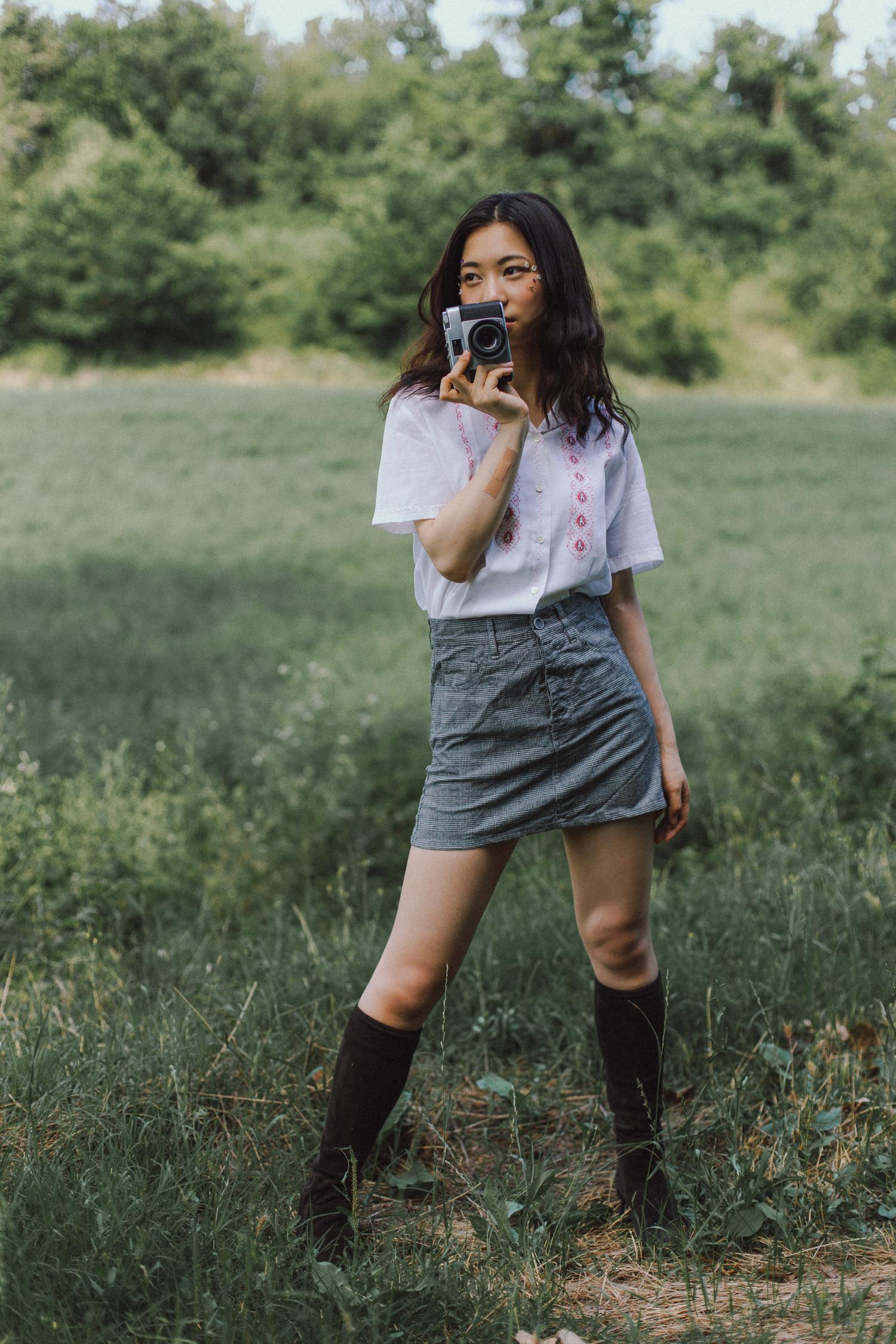 Ritratto di ragazza in piedi con macchina fotografica, gonna, camicia e fiori, anni '60