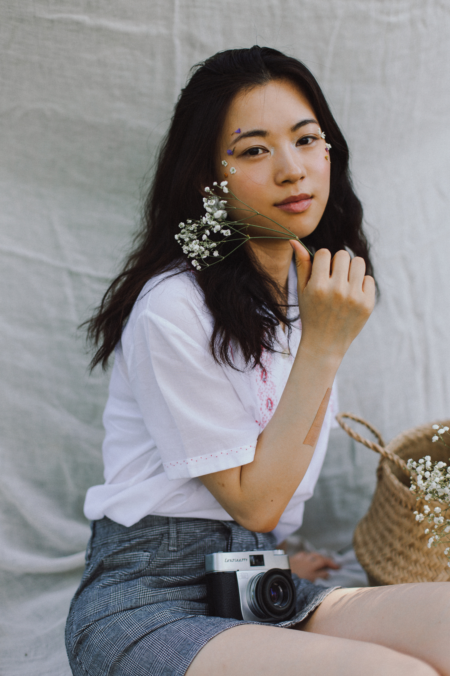 Ritratto di ragazza seduta con macchina fotografica vintage, gonna, camicia e fiori, anni '60