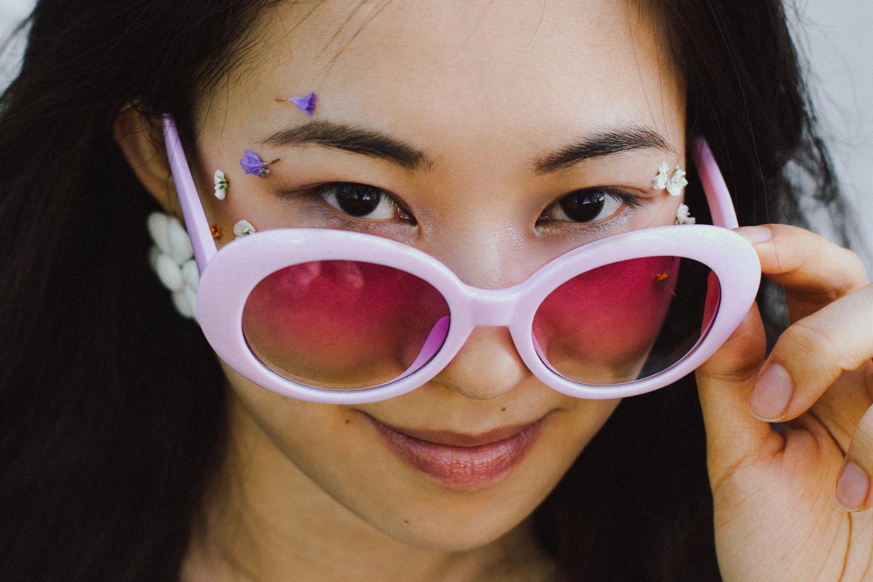 Ritratto di ragazza con occhiali da sole rosa anni '60 e trucco con fiori, dettaglio