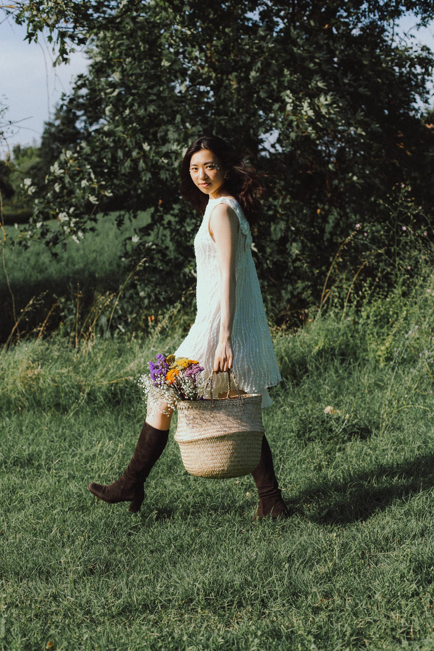 Ritratto di ragazza in piedi con vestito, stivali e fiori, anni '60