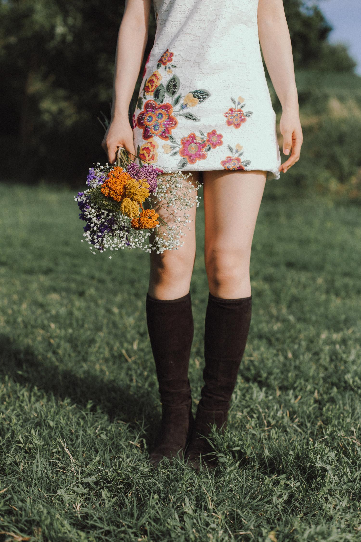 Foto di ragazza con stivali con vestito a fiori e mazzo di fiori, anni '60